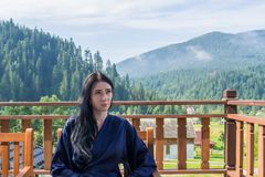Молодая женщина наслаждается ландшафтом горы, сидя в купальном халате на балконе стоковое изображение