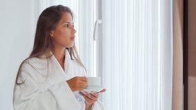 Молодая женщина наслаждаясь ее кофе утра около окна сток-видео