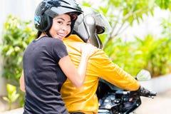 Молодая женщина наслаждаясь ехать на мотоцилк с ее парнем стоковые фотографии rf