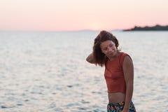Молодая женщина наслаждаясь заходом солнца морем Стоковое Фото