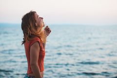 Молодая женщина наслаждаясь заходом солнца морем Стоковое Изображение RF