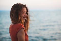 Молодая женщина наслаждаясь заходом солнца морем Стоковые Фото
