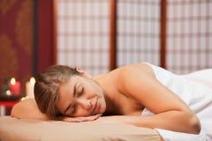 Молодая женщина наслаждаясь профессиональным массажем стоковое фото rf