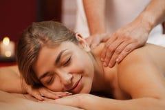 Молодая женщина наслаждаясь профессиональным массажем стоковая фотография