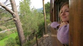 Молодая женщина наслаждаясь путешествовать на старом поезде, восхищая красивые туристские положения видеоматериал