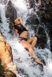 Молодая женщина наслаждаясь свежестью водопада стоковые фотографии rf