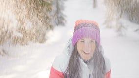 Молодая женщина наслаждаясь солнечным зимним днем, бросая снегом outdoors движение медленное акции видеоматериалы