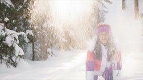 Молодая женщина наслаждаясь солнечным зимним днем, бросая снегом outdoors движение медленное видеоматериал