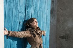 Молодая женщина наслаждаясь теплым солнцем зимы стоковое фото rf