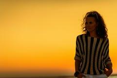 Молодая женщина на береге моря в вечере смотря в расстояние стоковое фото rf