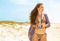 Молодая женщина на береге моря при ретро камера фильма смотря в сторону Стоковое Изображение