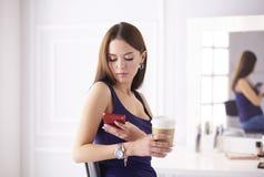 Молодая женщина на кофе кафа выпивая и говорить на мобильном телефоне стоковые фото