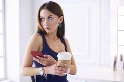 Молодая женщина на кофе кафа выпивая и говорить на мобильном телефоне стоковая фотография rf