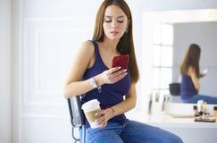 Молодая женщина на кофе кафа выпивая и говорить на мобильном телефоне стоковые изображения