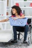Молодая женщина на кресло-коляске делая рутинные работы по дому стоковая фотография rf