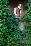 Молодая женщина на крылечке дома в деревне среди растительности Стоковое фото RF