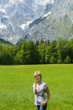 молодая женщина на луге с горами на заднем плане стоковая фотография
