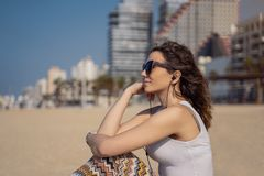 Молодая женщина на музыке пляжа слушая с наушниками Горизонт города как предпосылка стоковые изображения rf