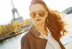 Молодая женщина на обваловке в Париже смотря в расстояние стоковое фото rf
