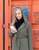 Молодая женщина на оранжевом контейнере используя smartphone Стоковые Изображения RF