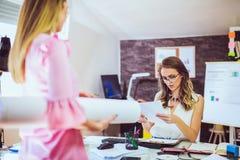 Молодая женщина 2 на офисе работая на новом дизайне Стоковые Фотографии RF