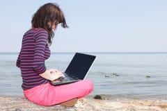 Молодая женщина на пляже с компьтер-книжкой Стоковая Фотография RF