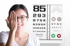 Молодая женщина на предпосылке диаграммы испытания зрения Зрение и глаз Стоковые Фотографии RF