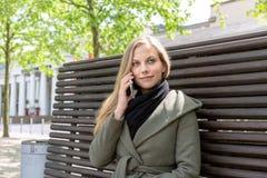 Молодая женщина на скамейке в парке используя smartphone Стоковые Изображения RF