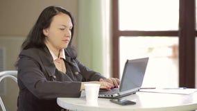 Молодая женщина на таблице в кафе, работая за компьтер-книжкой и выпивая кофе Медленный mo сток-видео