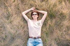 Молодая женщина на траве наслаждаясь весной стоковое фото