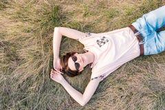 Молодая женщина на траве принимая время оценить весну стоковое фото