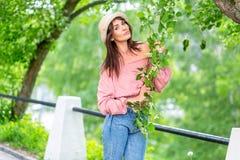 Молодая женщина на улице на солнечном вечере Красивая девушка в джинсах и небольшой шляпе держит цветя ветвь и смотрит стоковые изображения