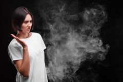Молодая женщина не любит дым сигареты или электронной сигареты на черной предпосылке лента измерения здоровья принципиальной схем стоковое фото rf