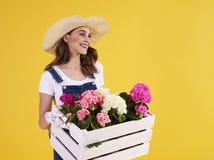 Молодая женщина нося деревянную клеть с красивыми цветками стоковое изображение