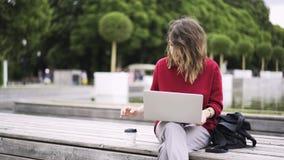 Молодая женщина нося красную работу с компьтер-книжкой около фонтана сток-видео