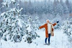 Молодая женщина нося теплые одежды имея потеху на лесе зимы стоковое фото rf
