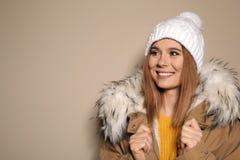 Молодая женщина нося теплые одежды на предпосылке цвета, космосе для текста готовая каникула стоковое фото rf