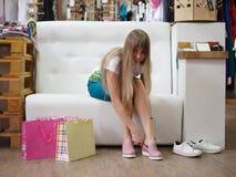 Молодая женщина одевая пару света - розовые ботинки на предпосылке магазина Блестящая девушка выбирая ботинки в магазине Стоковая Фотография