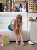 Молодая женщина одевая пару света - розовые ботинки на предпосылке магазина Блестящая девушка выбирая ботинки в магазине Стоковое Фото