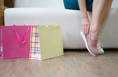 Молодая женщина одевая пару света - розовые ботинки на предпосылке магазина Блестящая девушка выбирая ботинки в магазине Стоковые Изображения