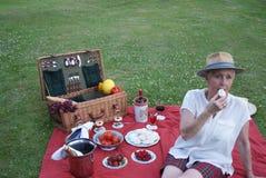 Молодая женщина, одетая в ее тартане Бермудских Островах управляющего, наслаждается меренгой для пикника стоковая фотография rf