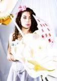 Молодая женщина одетая как Алиса в стране чудес с большими играя карточкой и цветками стоковое фото