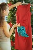 Молодая женщина около рождественской елки выбирая обмундирование рождества стоковая фотография