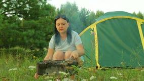 Молодая женщина около шатра жарит мясо на углях и выпивает чай акции видеоматериалы