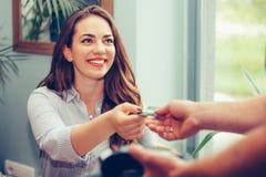 Молодая женщина оплачивает с кредитной карточкой для обеда на ресторане стоковые изображения