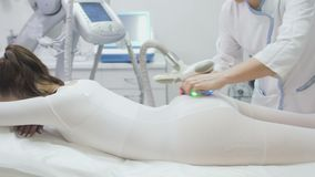 Молодая женщина ослабляет в клинике красоты во время массажа с прибором lpg видеоматериал
