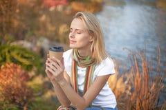 Молодая женщина ослабляет и наслаждающся выпивающ кофе на естественной предпосылке свежего воздуха утра стоковое фото