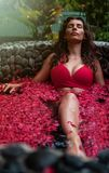 Молодая женщина ослабляя в на открытом воздухе ванне цветка, органической заботе кожи, роскошном спа в джунглях Внимательность кр стоковое фото