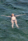 Молодая женщина ослабляя на море Стоковое Фото
