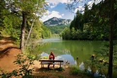 Молодая женщина ослабляя около озера и восхищая ландшафт стоковая фотография rf